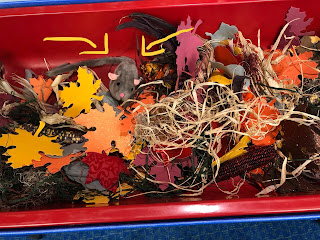sensory bin filled with textured paper leaves, straw, corn, sticks, mouse puppet and small flannel mice