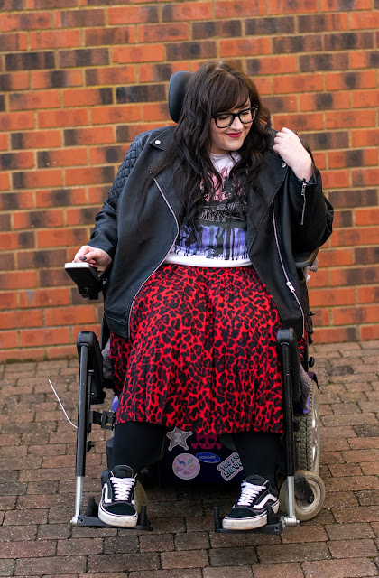 Plus size woman in wheelchair user wearing a black leather jacket, Stranger Things t-shirt, red and black animal print skirt, black tights and Vans