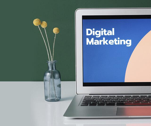 notebook em cima da mesa escrito marketing digital na tela