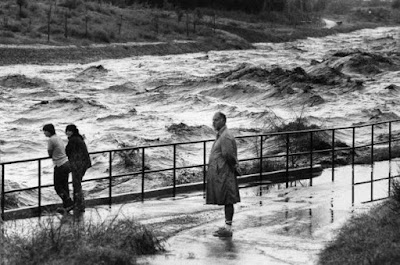 Black and white photo of 3 people standing by a guardrail looking at a raging river. Tucson, October 1983
