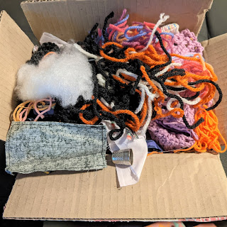 A small cardboard box overflowing with yarn, fabric, stuffing and string.