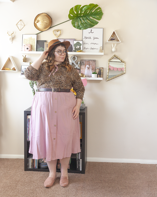 An outfit consisting of a brown panama hat, an animal print blouse tucked into a muted pink button down midi skirt and muted pink pointed mules.
