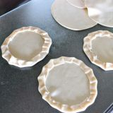 Crimping the edges of empanada rounds to make mini pizzas