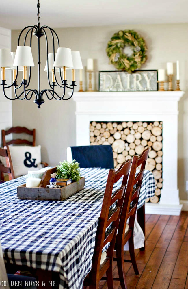 Neutral farmhouse style dining room with faux fireplace with stacked wood and Dairy sign