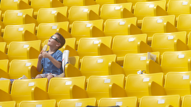 A little boy sits in a sea of yellow chairs