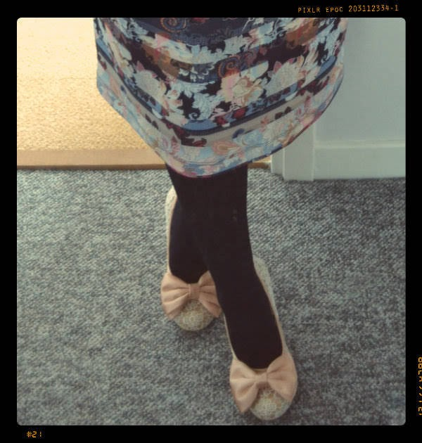 crossed legs wearing paisley dress black tights and nude lace heels