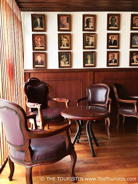 Old fashioned wooden brown armchairs and tables in front of three rows of photos