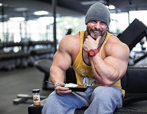 Hombre culturista con un plato de comida en el gimnasio