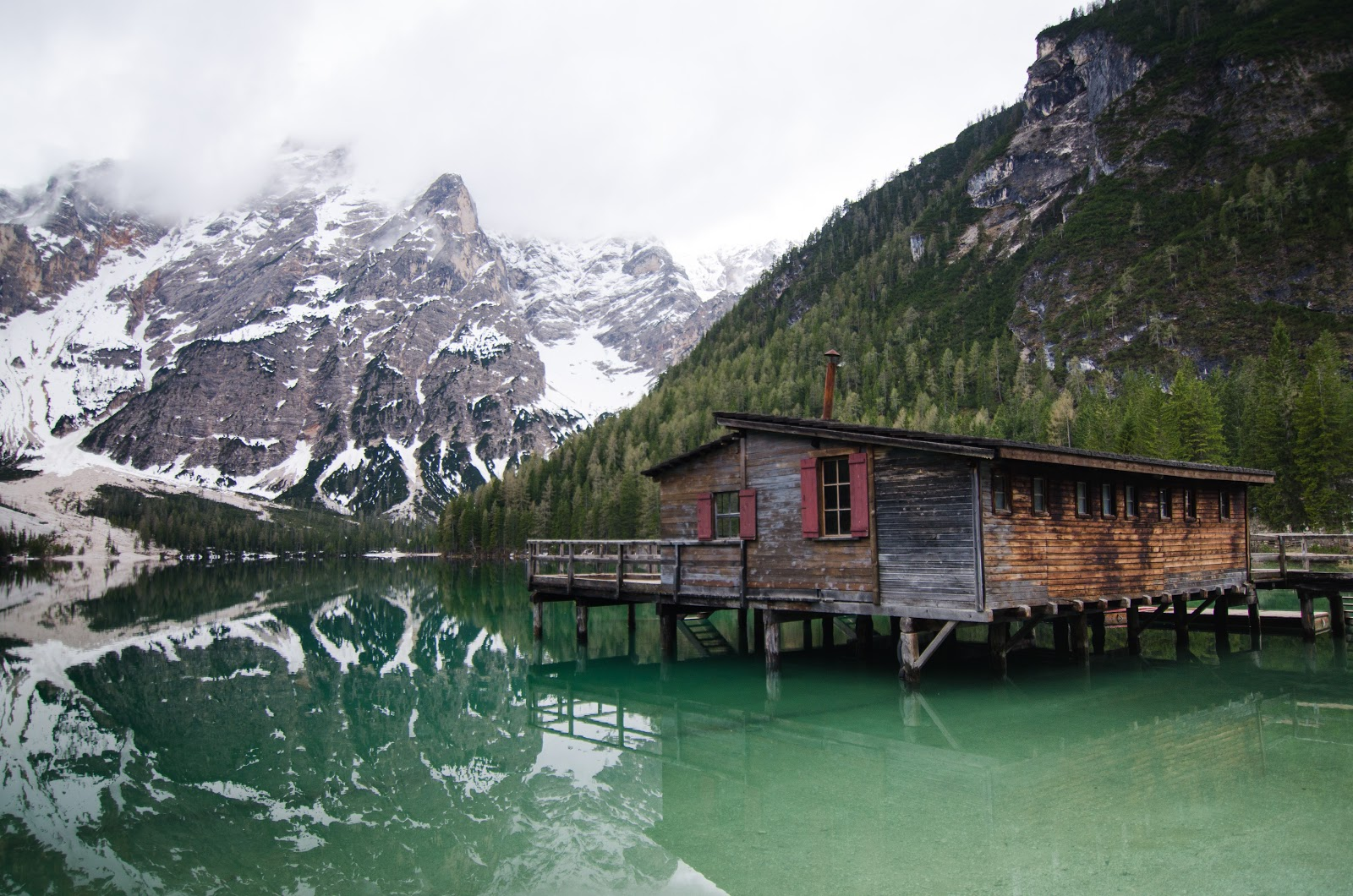 brown-wooden-house-on-lake-near-snow-covered-mountain-scenery-images