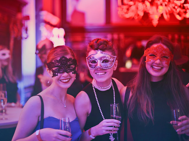 Three women wearing Mardi-gras masks at a party