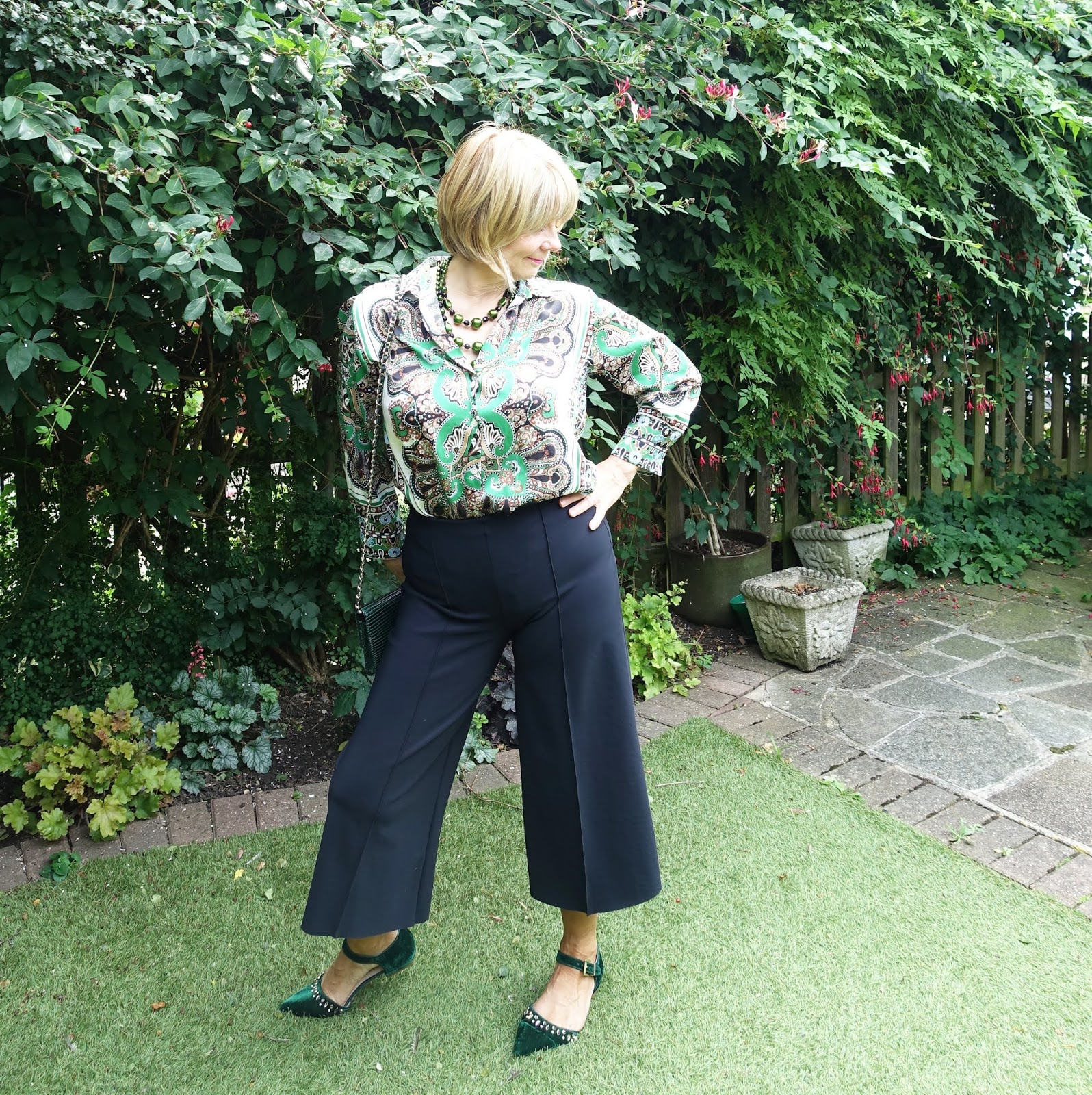 Mid life blogger Gail Hanlon in black and green for the office. Print blouse from Zara with cropped black trousers from Hope and green accessories.