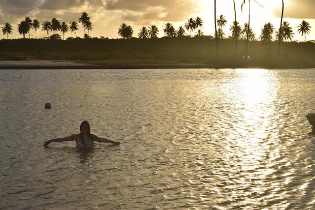 mulher tomando banho de rio no por do sol