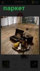 В помещении пол сделан из паркета, на котором стоит бутылка вина с фруктами и рюмка