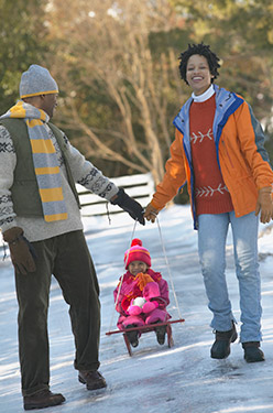 Parents pulling child on sled