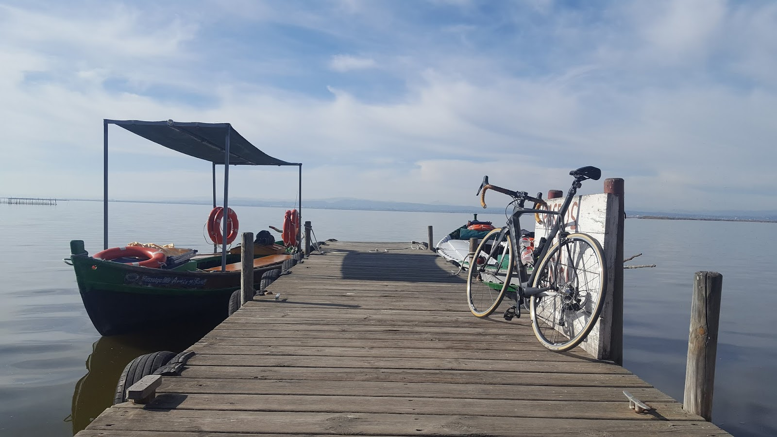 Bicycle and fishing boats on jetty at l'Albufera, Valencia, Spain