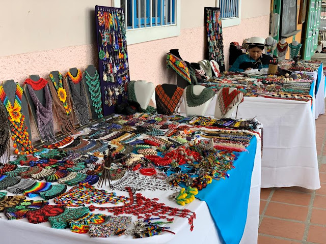 Three of the tables at the Saraguro market. Note earrings and other items available in addition to necklaces. Loja Ecuador