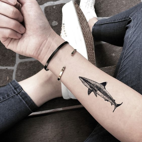What is the meaning of the shark tattoo pattern?