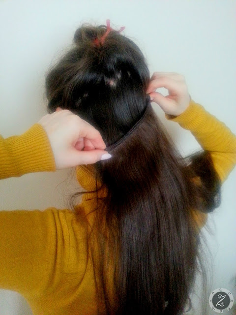 KROK 6: wypuszczamy kolejne pasmo naszych włosów, aby przykryło poprzednio doczepioną taśmę i postępujemy według tych samych kroków, aby dopiąć kolejne części