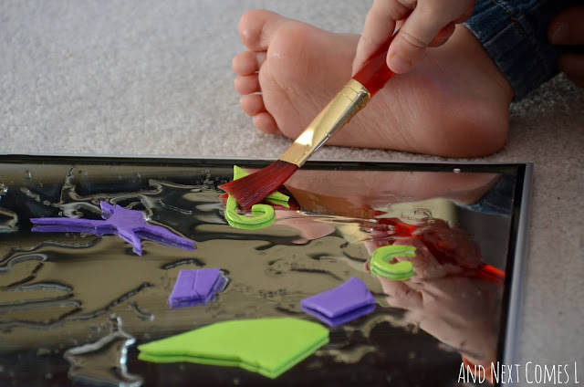 Toddler painting with water and decorating a mirror with craft foam