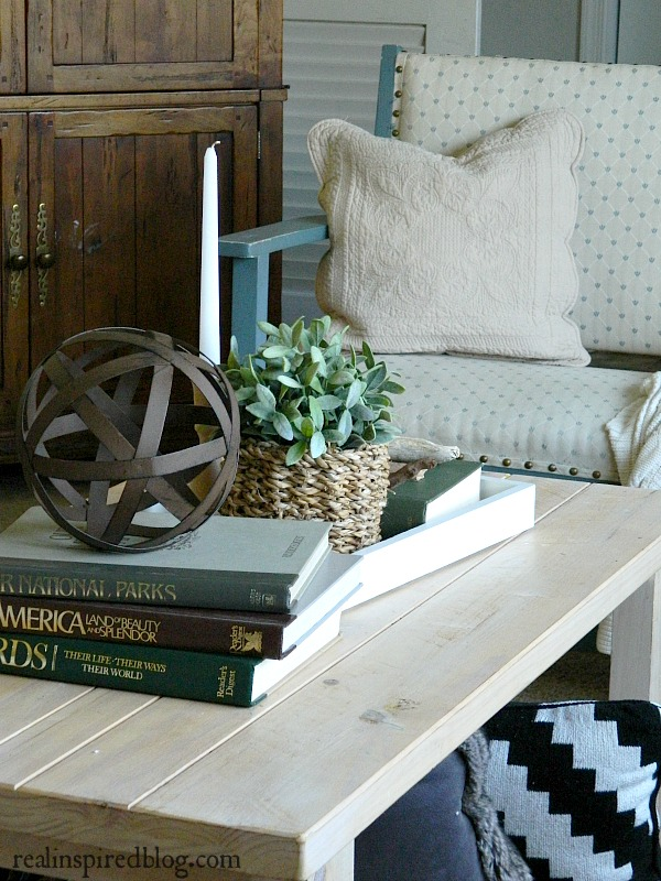 A cottage-like summer living room tour using whites, neutrals, and small pops of color in furniture and plants. Wood coffee table styled with candle, plant, baskets, books, metal orb sphere, and driftwood. Blue upholstered bench with quilted pillow.