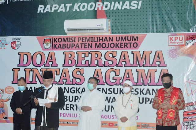 """Mojokerto - majalahglobal.com : Jelang Pilkada Kabupaten Mojokerto, Komisi Pemilihan Umum  (KPU) Kabupaten Mojokerto menggelar Doa Lintas Agama, Jumat (28/8/2020) di Gedung Pemilu 2019, Sooko Kabupaten Mojokerto.  Dalam sambutannya, Ketua KPU Kabupaten Mojokerto, Muslim Bukhori berharap agar Pilkada Kabupaten Mojokerto tahun ini bisa berjalan sukses.  """"Saya bersama KPU mengundang panjenengan semua berdoa bersama untuk kesuksesan Pilkada Mojokerto 9 Desember 2020. Semoga pilkada tahu ini bisa berjalan lancar, tanpa halangan apapun dan mendapatkan pasangan pemimpin yang amanah,"""" ujarnya.  Menurut pantauan majalahglobal.com, terlihat 5 tokoh agama yang membacakan doa, mulai dari Islam, Kristen, Protestan, Hindu dan Konghucu. Sementara untuk tokoh agama Budha berhalangan hadir. (Jayak)"""