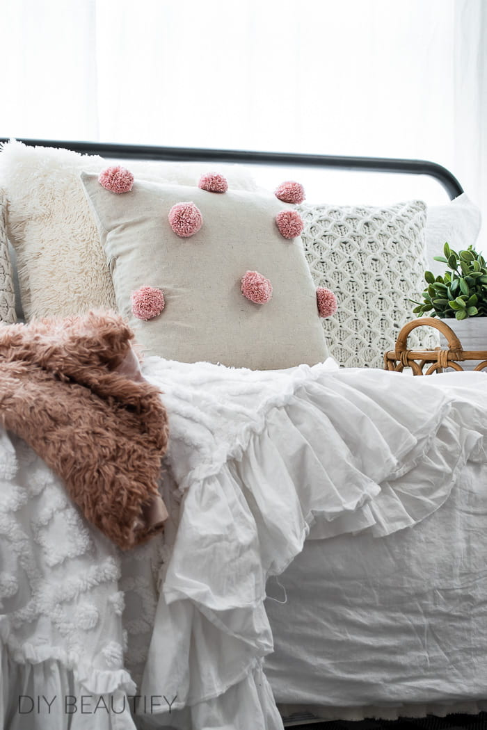 pom pom pillow and throws on cozy daybed