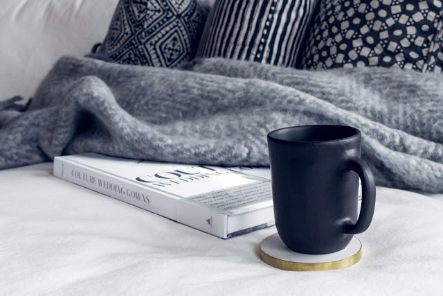 grey blanket, white book and black mug on coaster