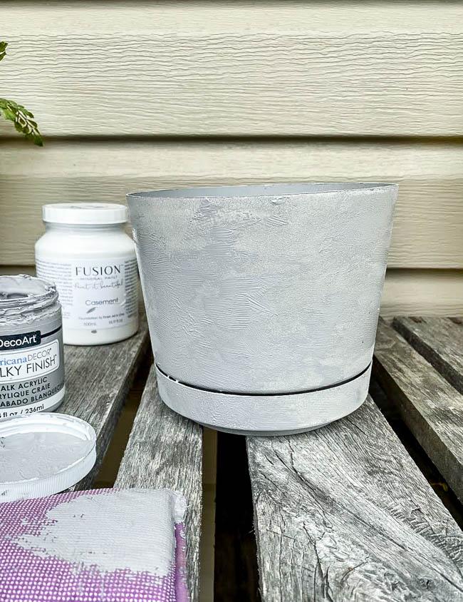 dab on dark gray paint in various areas around planter