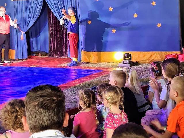 Image of Happy's Circus Ring at Gloworm Children's Festival 2021. The image shows a circus ring and a crowd of seated children around the edge. In the ring is a clown and the ring master holding lanterns in front of blue curtains.