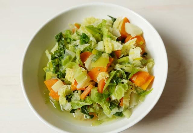 Wirsing-Eintopf im Teller mit Karotten, Lauch und Brühe