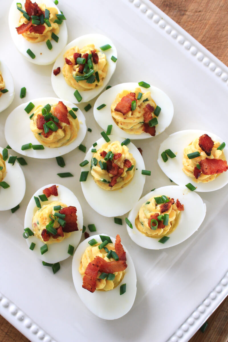 Loaded Deviled Eggs are fully loaded with cheddar cheese, bacon, chives, and horseradish mustard. You will want to serve them at every holiday and party! #appetizer #deviledeggs