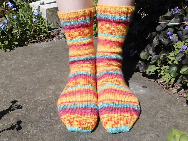 A pair of orange striped hand knitted socks being modelled on feet.  The feet are facing the view and the model is standing on a stone slab