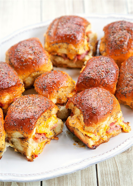 Hot Ham and Pimento Cheese Sandwiches - Hawaiian rolls, ham, pimento cheese topped with a sweet and savory butter poppy seed sauce and baked. SOOOO good! These are so easy to assemble - only takes a few minutes. Perfect for brunch, lunch or dinner. There are never any left! A new favorite!