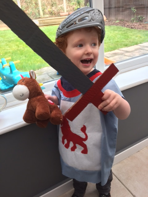A toddler playing as a knight