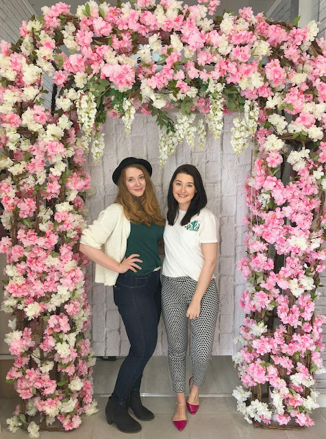 two ladies posing under floral archway at the scouse bird salon, liverpool
