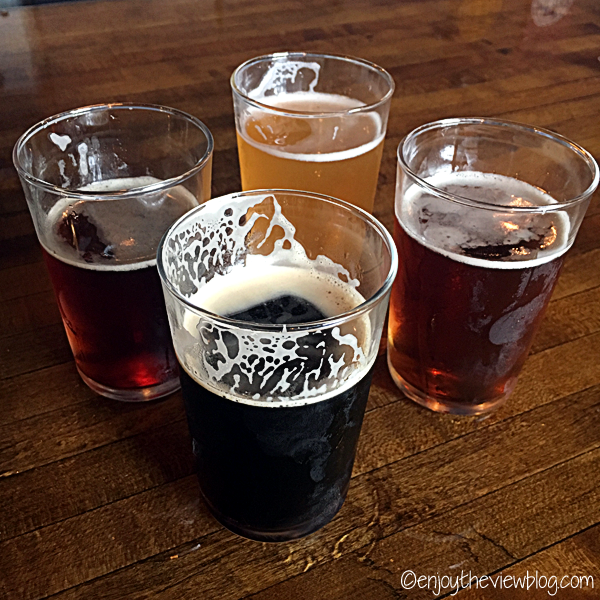 four small glasses of different types of beer sitting on a wooden bar