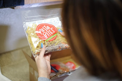 """Graphic shows a woman holding a bag of pasta which reads, """"Pasta Bites"""""""