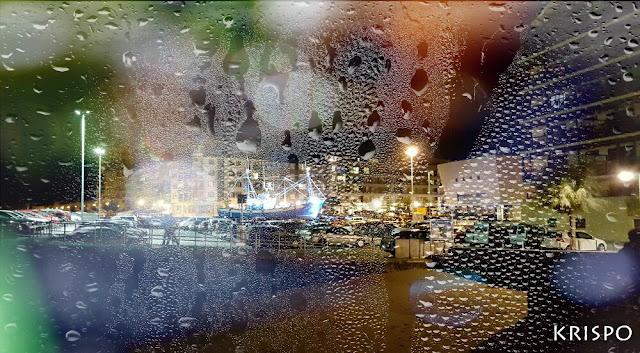 paisaje nocturno de hondarribia a través de una ventana mojada por la lluvia