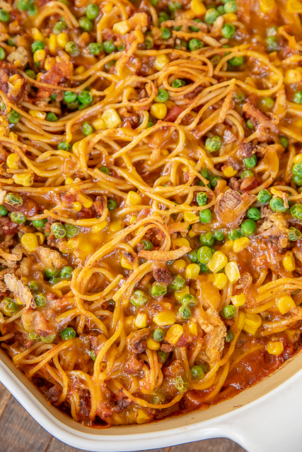 baked spaghetti with corn and peas in casserole dish