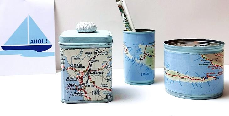 drei mit Landkarten beklebte Blechdosen