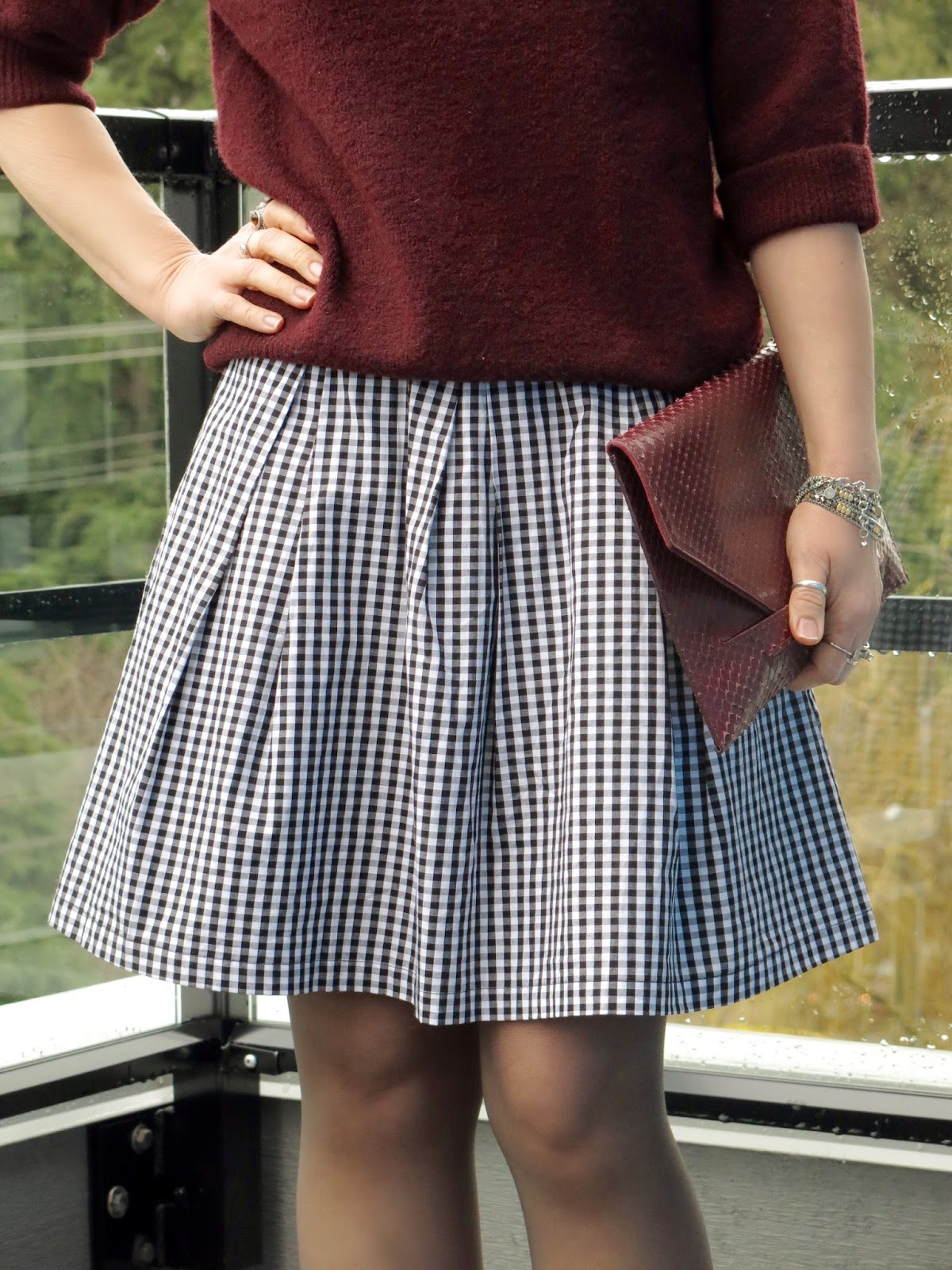 maroon turtleneck, gingham skirt, and faux-snake envelope clutch