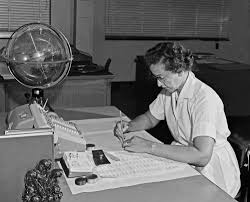 Black and white image of Katherine Johnson working at desk.