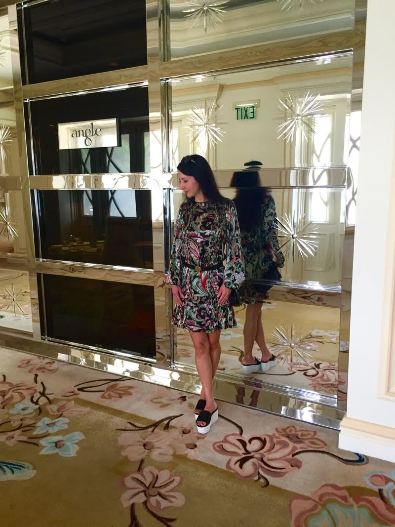 Wearing a printed dress, black belt, black crossbody bag, black sunglasses, and black flatform shoes. Standing in front of a mirrored wall.
