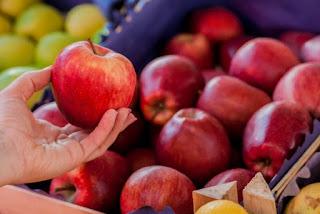 mão pegando uma maçã vermelha linda