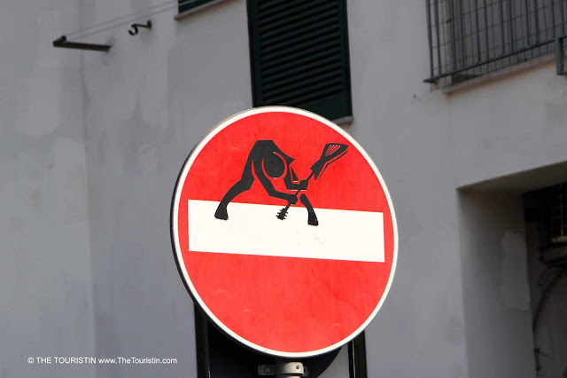 A sticker of a guitar player smashing his guitar on the ground stuck on a regular No entry-street sign.