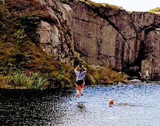 Lisa Southard jumping off a rock, mid air, before the big splash