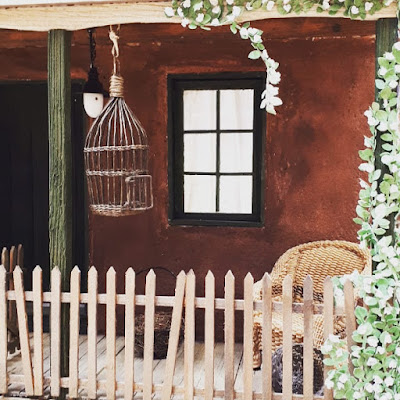 One-twelfth scale miniature Australian cottage porch with a bird cage and a woven chair