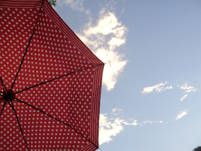 Céu, sombrinha vermelha com bolinhas