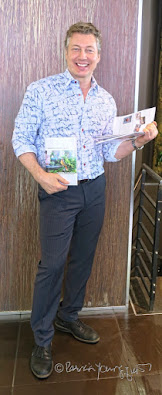 "his picture features a man in his mid fifties holding volumes one and two of my book series, ""Words In Our Beak."" He has blonde curly hair, blue eyes and is smiling broadly as he stands up holding the books. Volume two is in his right hand (or left side of the photo) and it is closed but the cover is facing front. In his right hand (or left side of the photo) he is holding volume one and the book is open.   Information re these book as well as info re volume three is on my blog @ https://www.thelastleafgardener.com/2018/10/one-sheet-book-series-info.html"