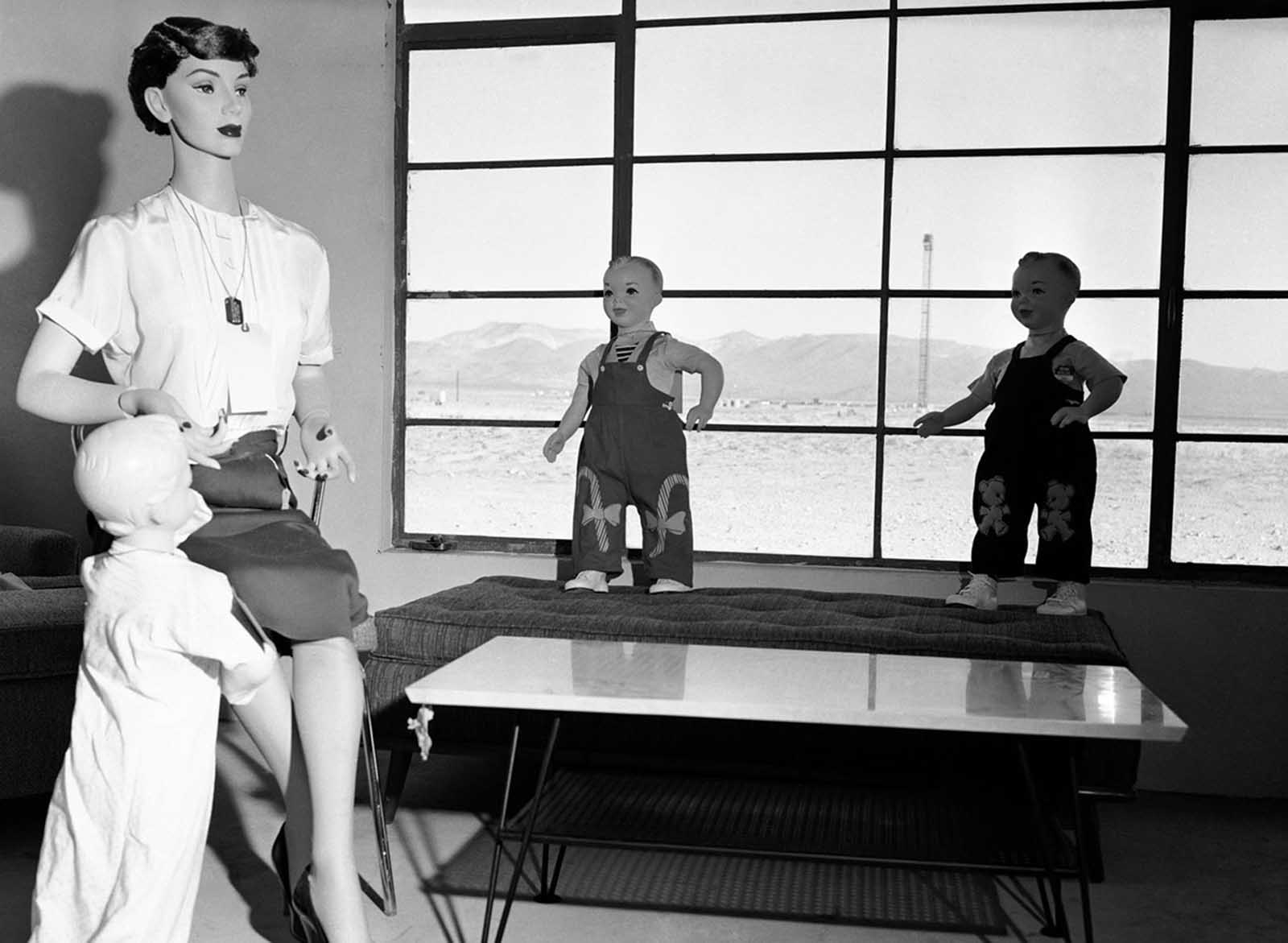 Mannequins that represent a typical American family will soon experience the fury of an atomic blast with the power of 40,000 tons of TNT at Yucca Flat, Nevada, on April, 24, 1955. The test is being conducted to determine the survival chances of an atomic attack. Visible through the window is the tower 4,700 feet away on which the detonation will occur.